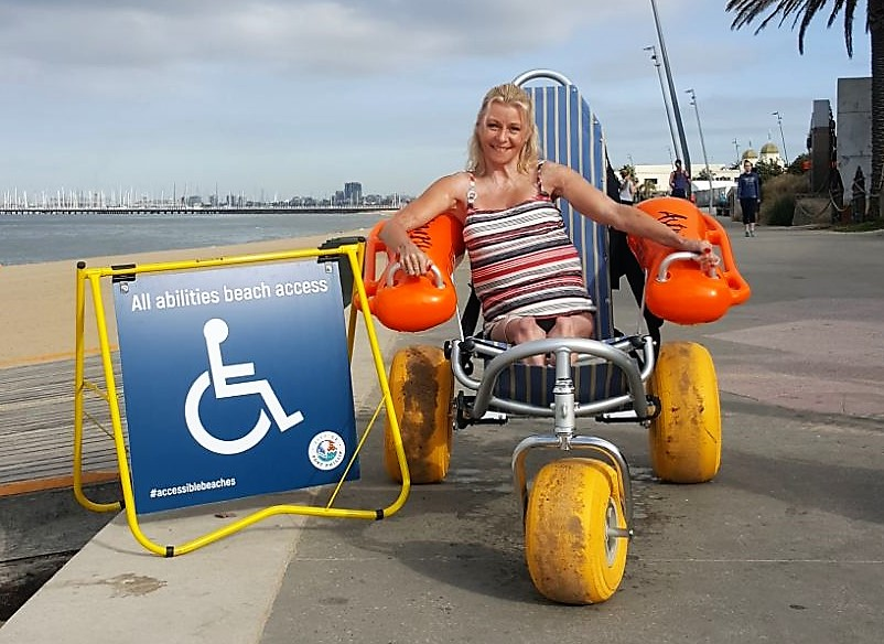 Amanda in the beach wheelchair, with a sign next to her saying accessible beach